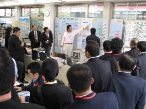 次に事務所の見学です サービス作業管理ボードなどの工程管理ツールについて 説明しています
